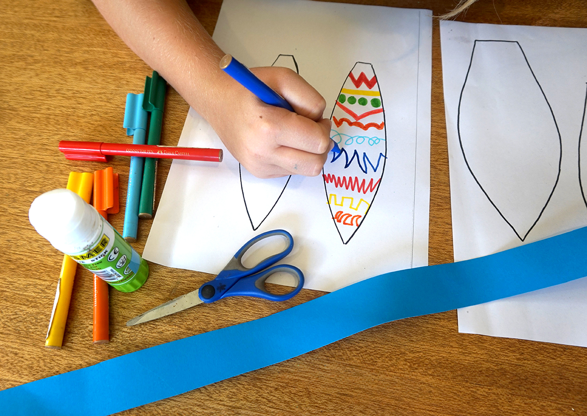 Boy using coloured textas to decorate paper bunny ear template.