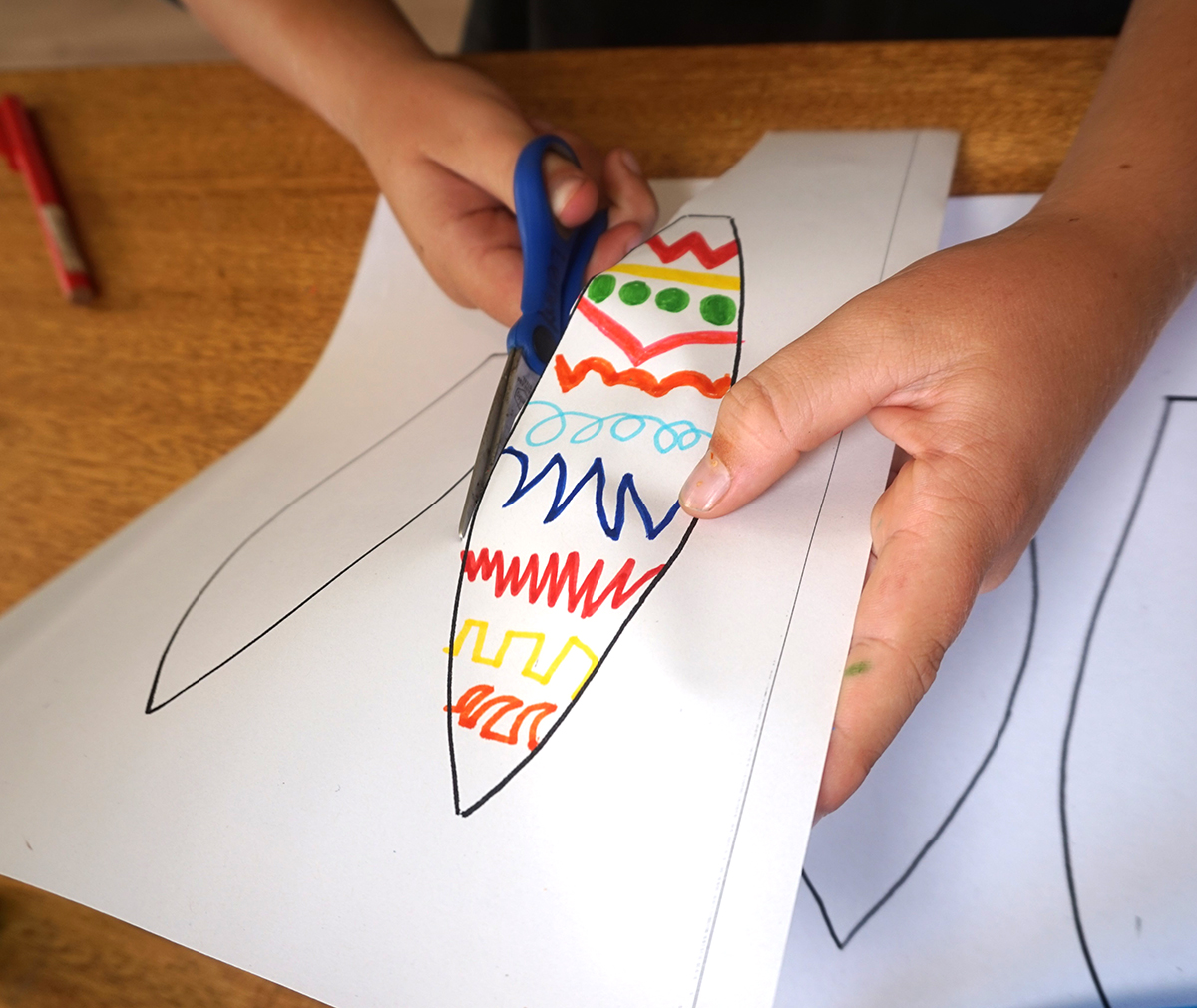 Boy using scissors to cut out paper bunny ear template.