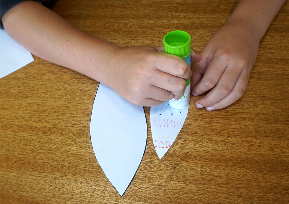 Boy using glue stick to apply glue to the back of the inner ear part of the paper template.