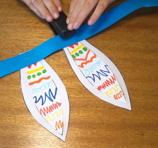 Boy stapling the flat base end of the paper ears onto the paper ribbon slightly apart.