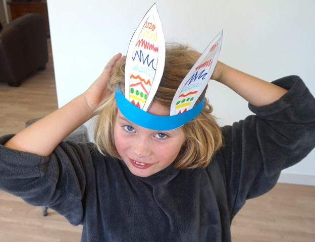 Boy wrapping paper ribbon around head circumference to check for fit.