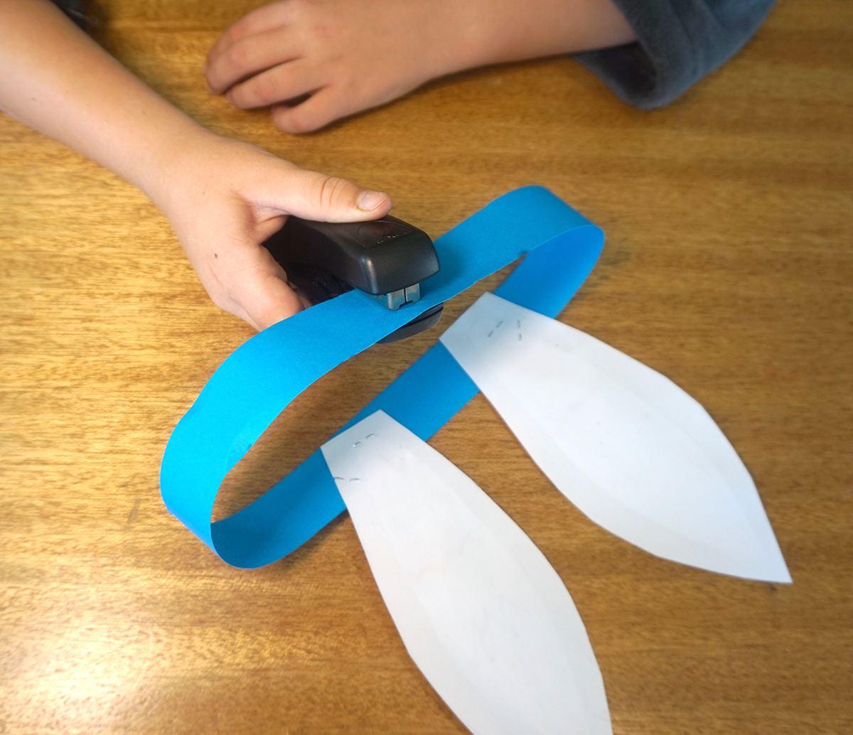 Boy stapling paper ribbon ends together to form a circle.