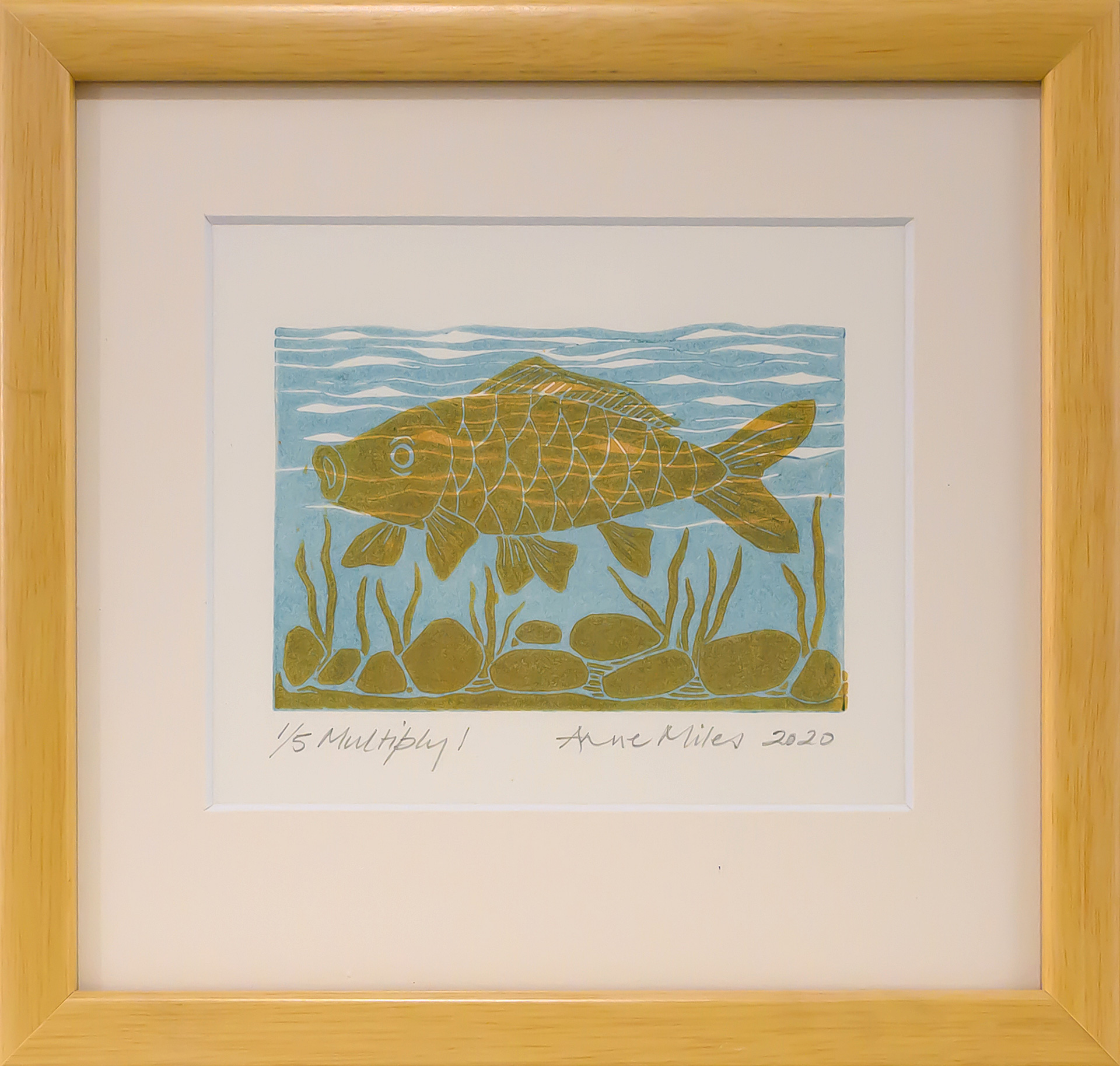 Framed artwork by Anne Miles of a yellow Carp with rocks and weeds in a blue water background