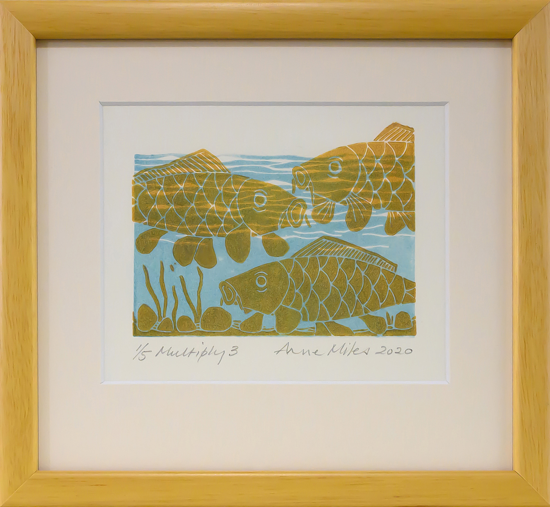 Framed artwork by Anne Miles of 3 yellow Carp with rocks and weeds in a blue water background