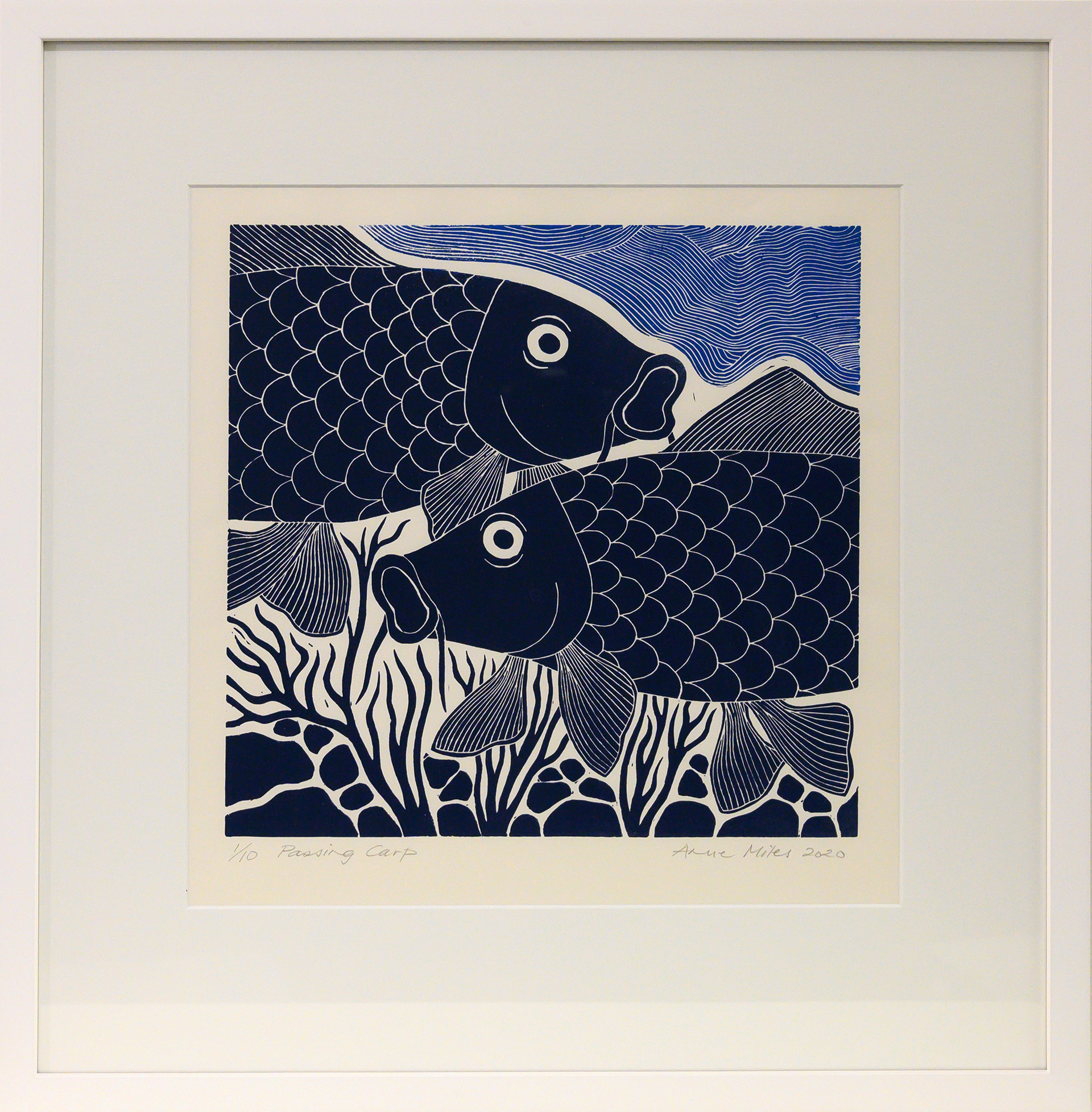 Framed artwork by Anne Miles of 2 dark blue Carp with rocks and weeds and lighter blue swirly water