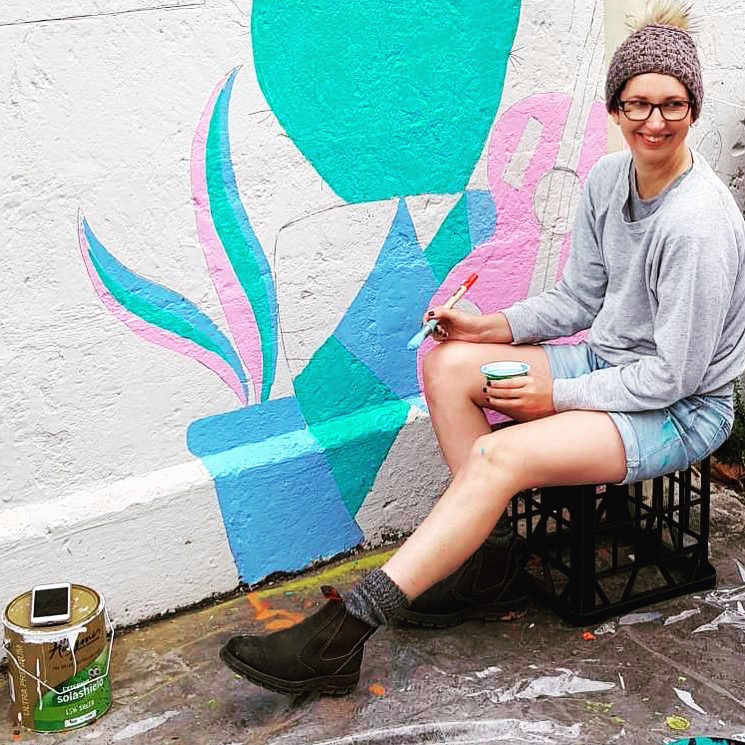 Lady sitting next to wall painting mural.