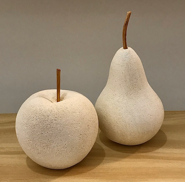 Limestone life size apple and pear sculptures with applewood stems.