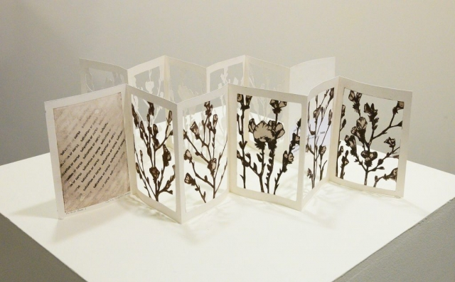 Folded concertina style artist book by Julie Bignell, featuring 5 panels with hand cut b&w flowers and 1 panel with text