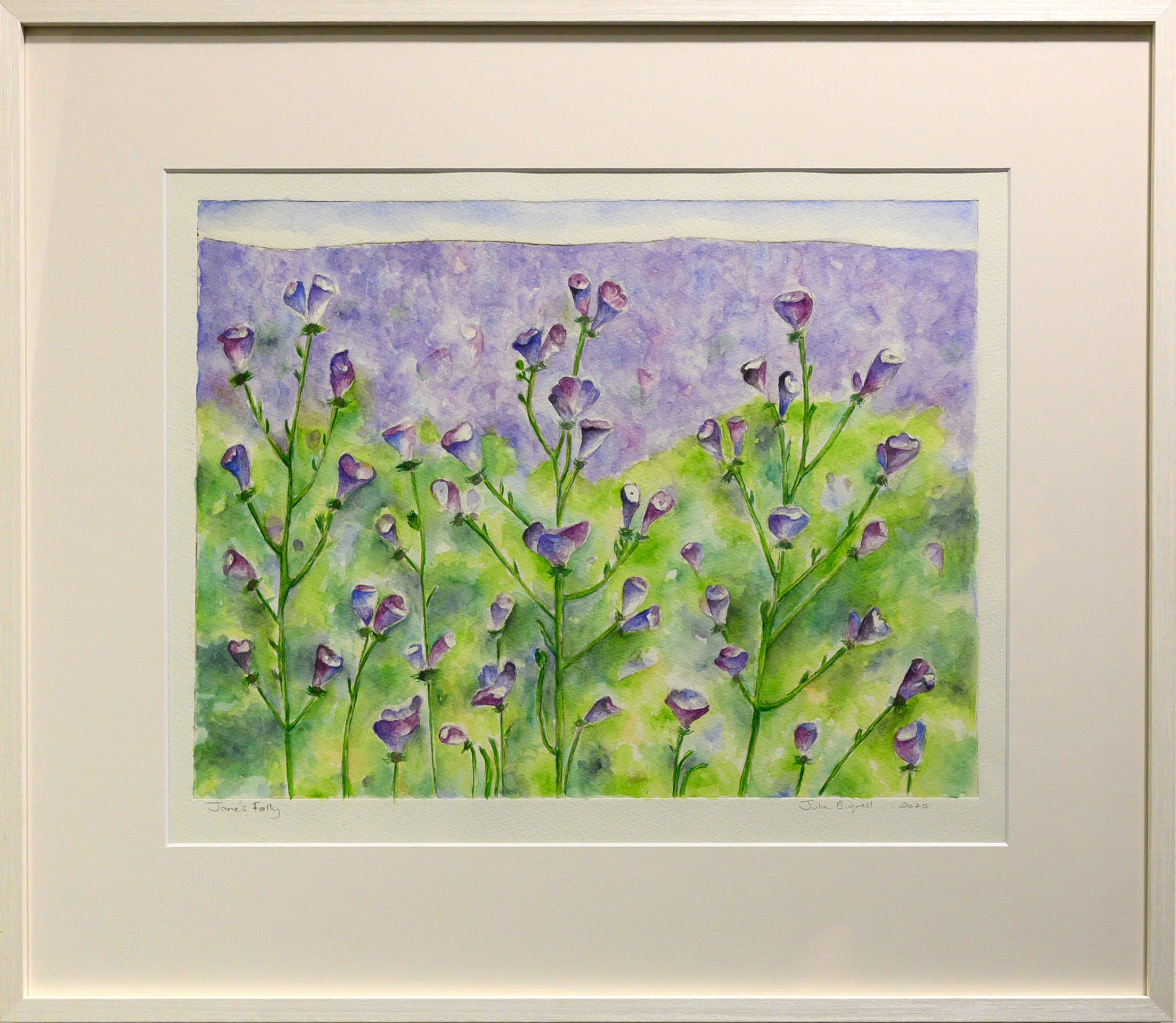 Framed artwork by Julie Bignell of purple flowers in the foreground with a green and purple background