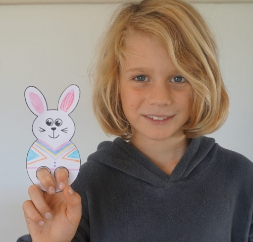 Boy demonstrating finished bunny puppet.