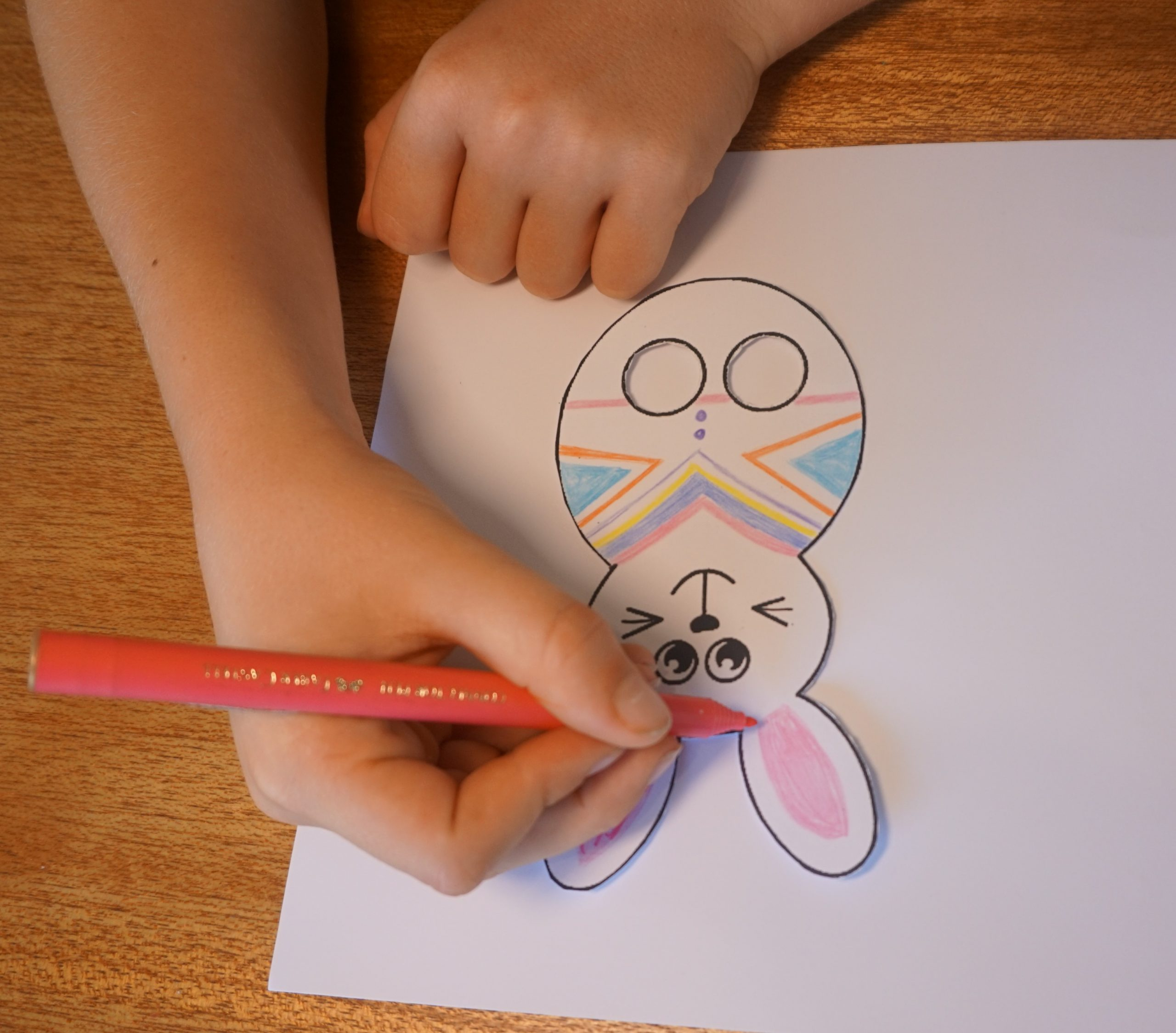 Boy using coloured textas to decorate paper bunny finger puppet template.