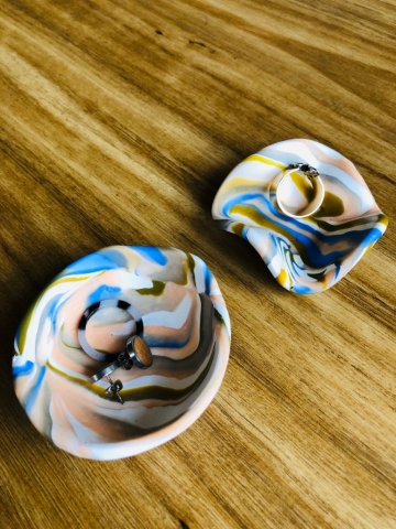 Colourful marbled polymer clay bowls holding rings