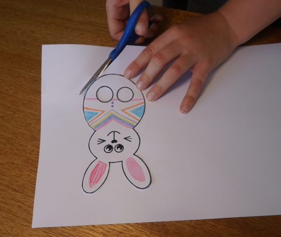 Boy using scissors to cut out the paper bunny finger puppet template including the two circles where the fingers will go to use the puppet..