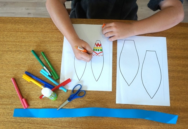 Boy colouring in bunny ear with textas while the rest of the required equipment sits on table including Paper Templates, Scissors, Glue Stick, Paper Ribbon, Coloured Textas and a Stapler
