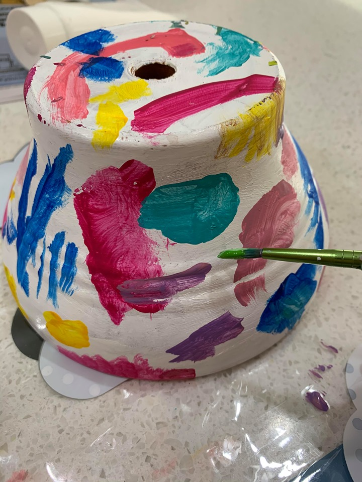 A white garden pot with colourful paint splotches.