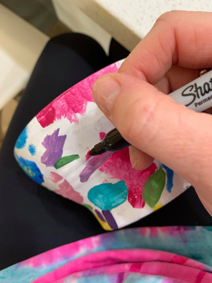Black Sharpie  pen to draw shapes over colourful splotches on white garden pot.