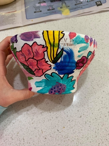 A white garden pot with colourful paint splotches and sharpie pen outlines.
