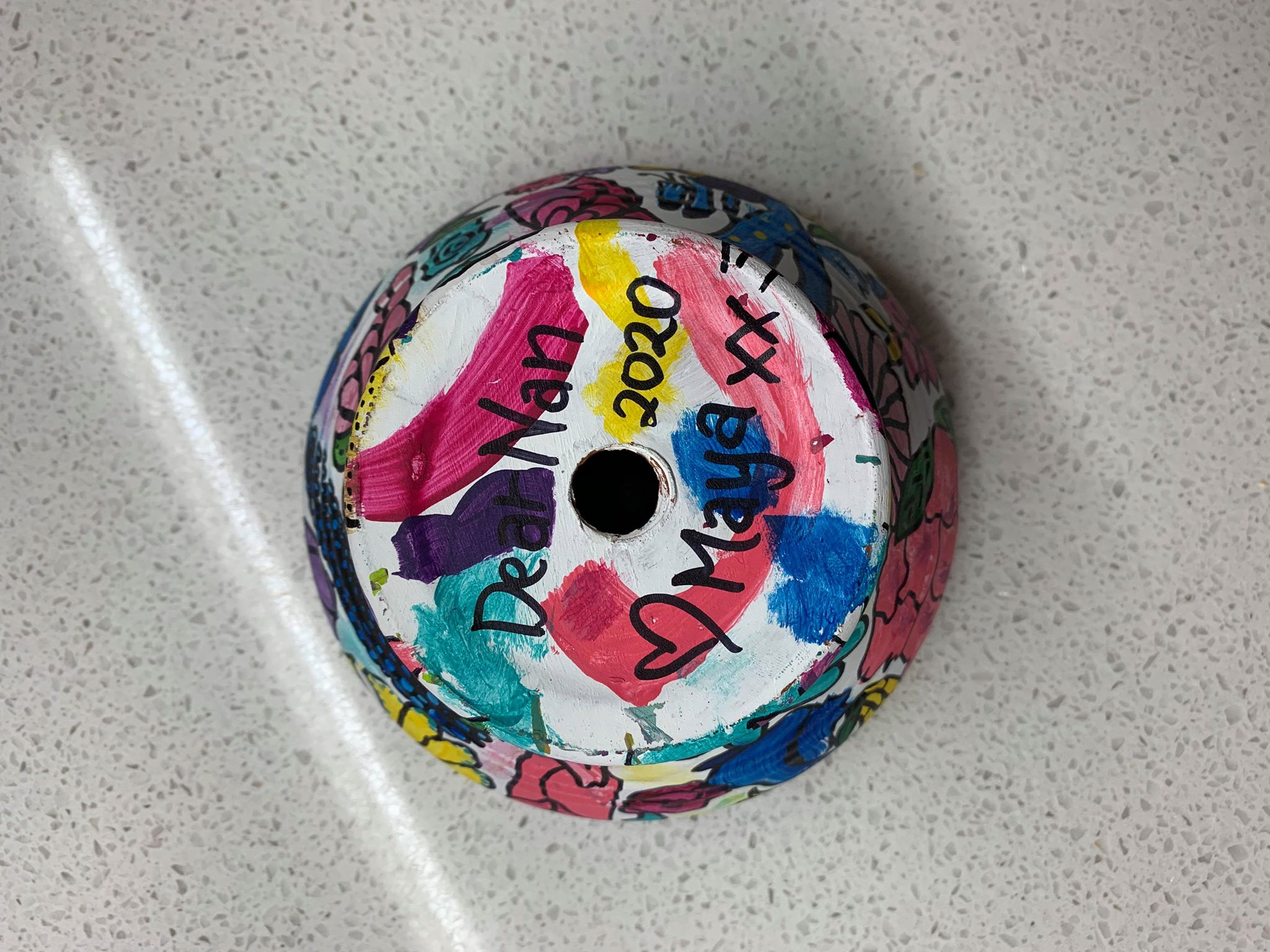 A white garden pot with colourful paint splotches and sharpie pen outlines with a sharpie message on the base.