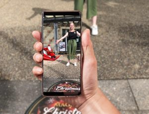 Hand holding phone showing Augmented Reality on screen